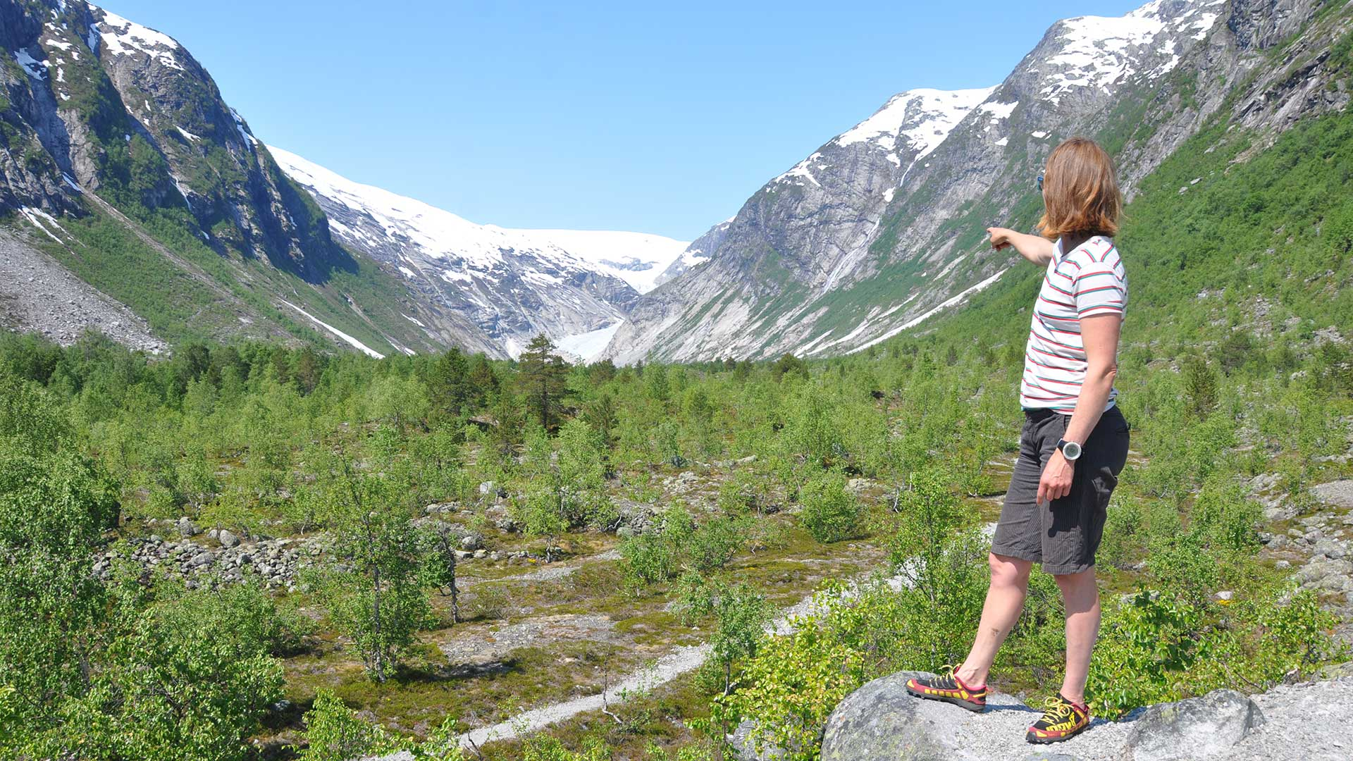 Woman pointing at a glacier.