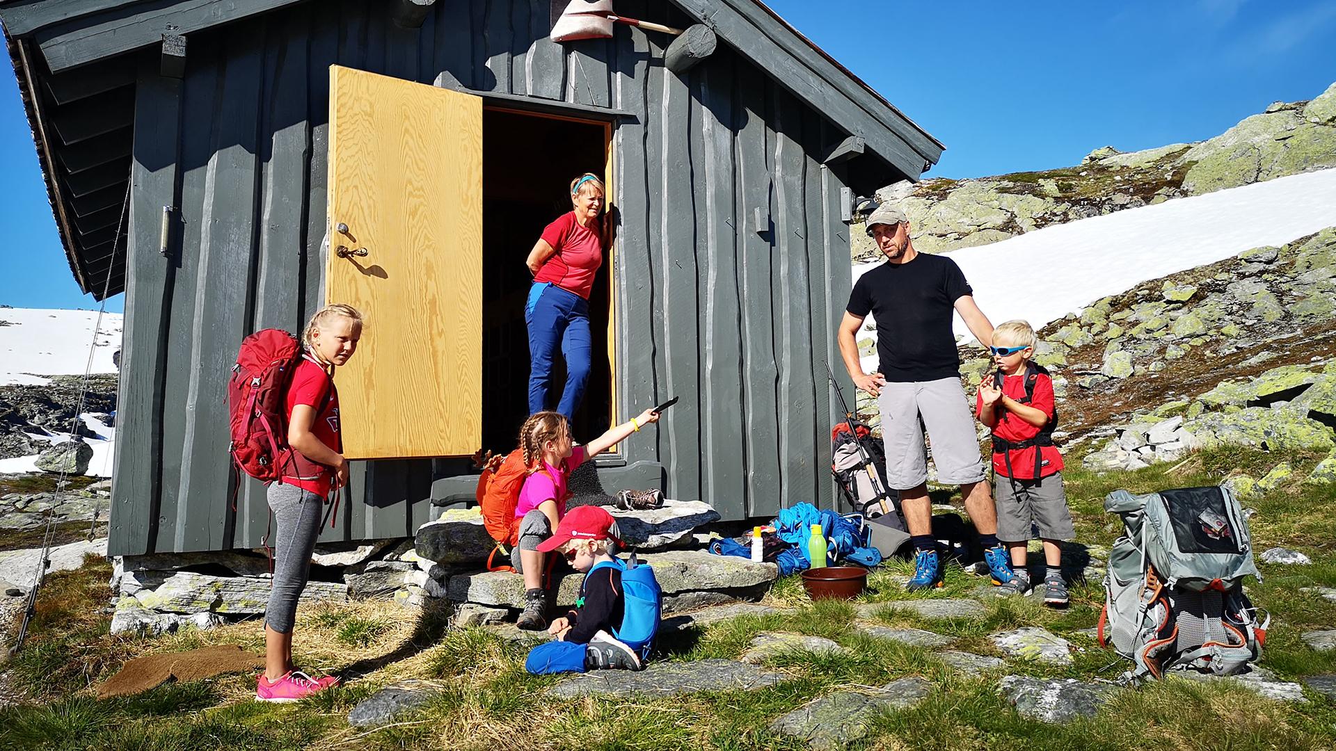 Familie foran en hytte i fjellet.