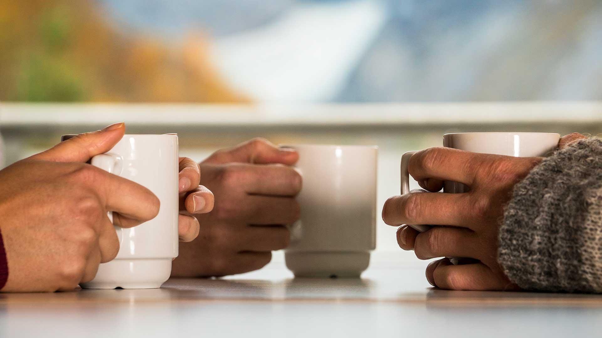 Hender som holder tre kaffekopper.