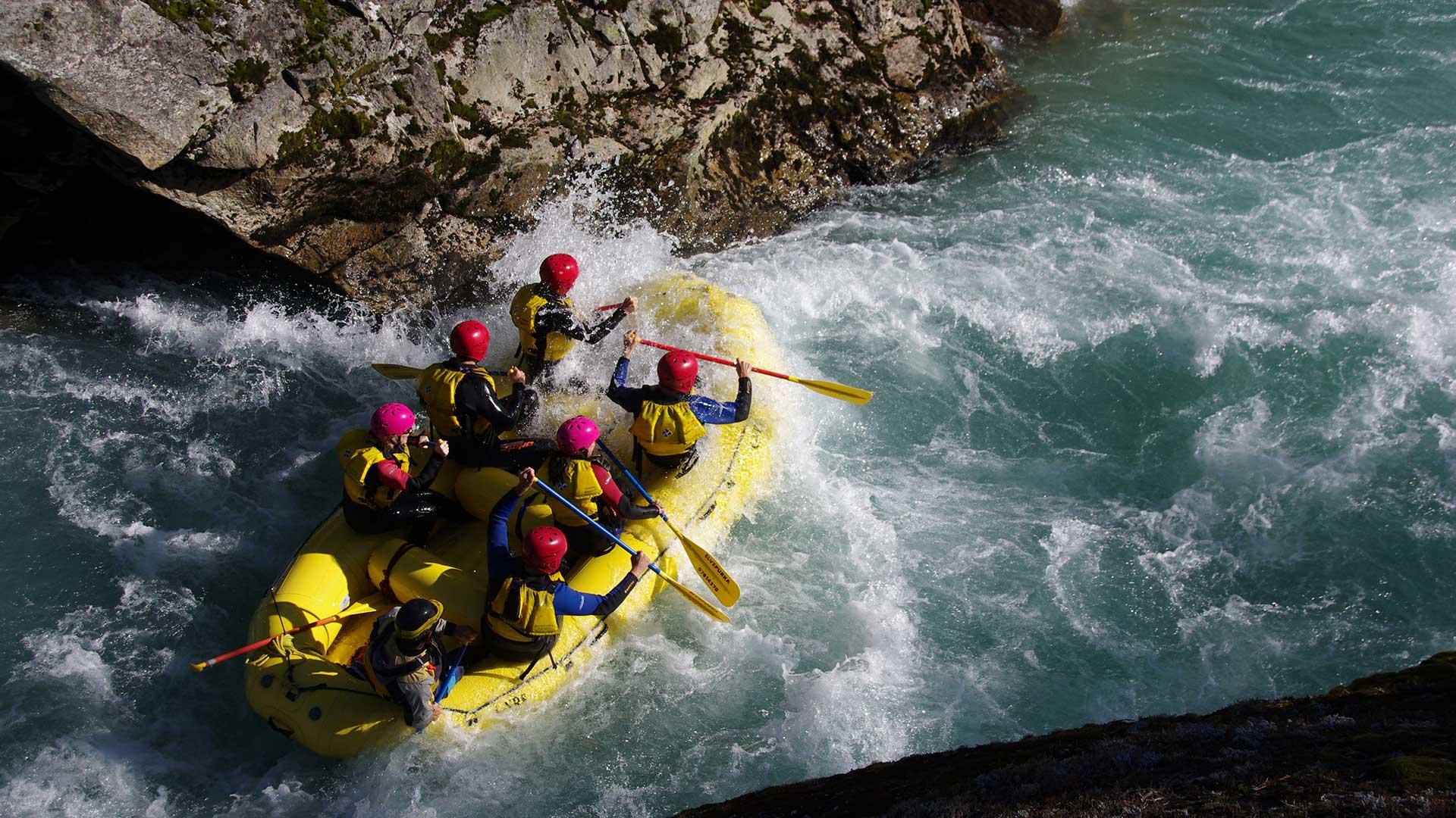 Mennesker i raftingbåt i frådende elv